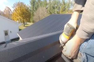 Worker installing a metal roof on a residential roof.