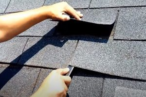 Worker for Kitchener Roofing checking that all shingles on residential roof are good.